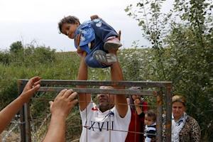 A Syrian migrant lifts a child over a fence on the Hungarian-Serbian border near Asotthalom
