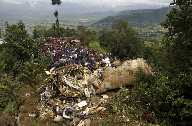 Nepalese rescue workers and civilians gather around the wreckage of a Beechcraft 1900D operated by Buddha Air after it crashed in the mountains outside Bisankunarayan village, just south of Katmandu,