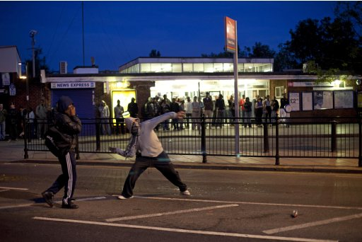 FILE -Youths throw bricks at police in this Sunday, Aug. 7, 2011 photo  during unrest in Enfield, north London. Nearly 1,200 people have been arrested since the riots erupted Saturday, mostly poor youths from a broad section of Britain's many races and ethnicities.  Britain is bitterly divided on the reasons behind the riots _ some blame the unrest on opportunistic criminality, while others say the country's economic policies and cuts have deepened inequalities in the most deprived areas.(AP Photo/Karel Prinsloo, File)