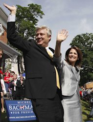 FILE - In this June 27, 2011, file photo Rep. Michele Bachmann, R-Minn., and her husband Marcus wave to the crowd after her formal announcement to seek the 2012 Republican presidential nomination in Waterloo, Iowa. Marcus Bachmann is defending his Christian counseling business for offering so-called ex-gay therapy, a controversial practice that's focused attention on the Bachmanns' views on social issues at a time when the Minnesota congresswoman has shown momentum in the Republican presidential race. (AP Photo/Charlie Riedel, File) )