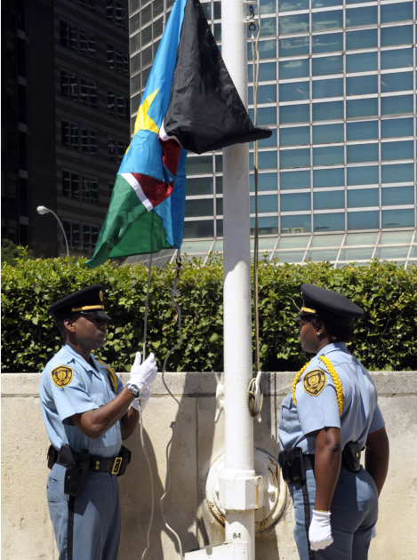 In this photo provided by the United Nations, the national flag of the Republic of South Sudan is raised by two United Nations Security Officers, Thursday, July 14, 2011, marking the country's admissi