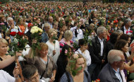 People hold up flowers during a vigil in memory of the eight people killed in Friday's blast in Oslo and the 68 who died in the shooting at the youth camp on Utoya, in Vik, near Sundvollen close to Utoya island, near Oslo, Norway, Tuesday, July 26, 2011. (AP Photo/Ferdinand Ostrop)