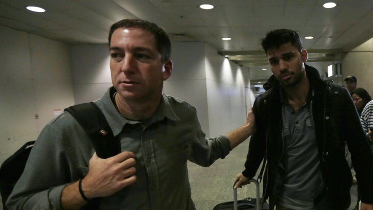 U.S. journalist Greenwald walks with his partner Miranda in Rio de Janeiro's International Airport