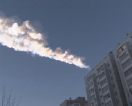 The trail of a falling object is seen above a residential apartment block in the Urals city of Chelyabinsk, in this still image taken from video shot on February 15, 2013. A powerful blast rocked the Russian region of the Urals early on Friday with bright objects, identified as possible meteorites, falling from the sky, emergency officials said. REUTERS/OOO Spetszakaz (RUSSIA - Tags: ENVIRONMENT TPX IMAGES OF THE DAY)