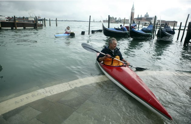 A man rows a kayak in front of flooded St. Mark's Square during a period of seasonal high water in Venice