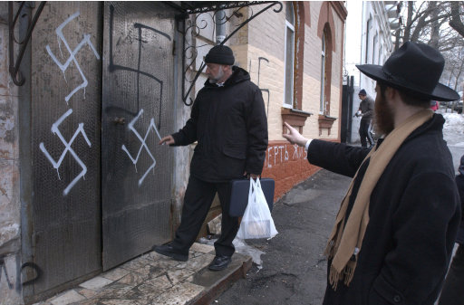 FILE  - In this March 2, 2007 file photo, head of the Jewish community Gennady Klebanov, left, is about to enter the swastika-smeared door of the synagogue, as chief rabbi of Vladivostok and the Far Eastern Primorsky region, Isroel Silberstain, right, points in the Russian Far Eastern Port of Vladivostok, 9,300 kilometers (some 5,750 miles) east of Moscow. Swastikas and anti-Semitic slogans were painted on the Vladivostok synagogue.  They beat up black and Arab football fans, terrorize immigrant neighborhoods, smash Muslim and Jewish gravestones, preach hate and rally support online. Norway's attacks laid bare a fringe of flourishing racist anger around Europe _ and exposed the risk that it could erupt into violence anywhere, anytime. Europe's right-wing extremists are exceptional voices, numbering in the thousands. But their voices can take on disproportionate weight and skew perceptions of immigration. (AP Photo, File)