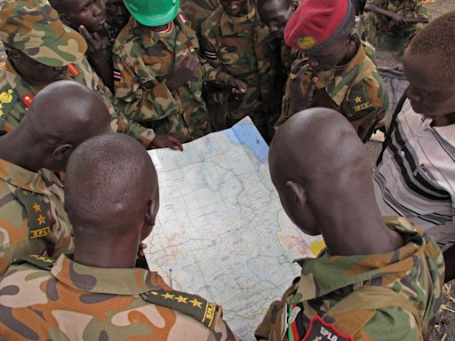 Soldiers from the Sudan People's Liberation Army (SPLA) examine a map at the frontline position in Pana Kuach, Unity State, South Sudan, Friday May 11 2012. In late April, tensions between Sudan and South Sudan erupted into conflict along their poorly defined border. Thousands of SPLA forces have been deployed to Unity State where<br /><br /><br /><br /><br /><br /><br /><br /><br />  the two armies are at a tense stalemate around the state's expansive oil fields. Fighting between the armies lulled in early May after the U.N. Security Council ordered the countries to resume negotiations. (AP Photo/Pete Muller)