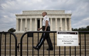 A US Park Police officer walks behind a barricade with …