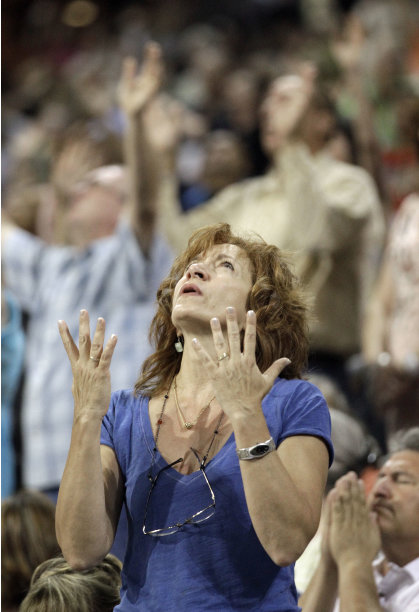 A woman prays at The Response, a call to prayer for a nation in crisis, Saturday, Aug. 6, 2011, in Houston. Texas Gov. Rick Perry attended the daylong prayer rally despite criticism that the event inappropriately mixes religion and politics. (AP Photo/David J. Phillip)