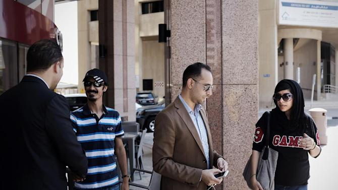 Bahraini human rights activist Zainab al-Khawaja (R), sister of jailed activist Maryam al-Khawaja, lawyer Mohammed al-Jishi (2-R) and Zainab's husband Wafi al-Majed (2-L), near the Bahrain court building in Manama on September 6, 2014