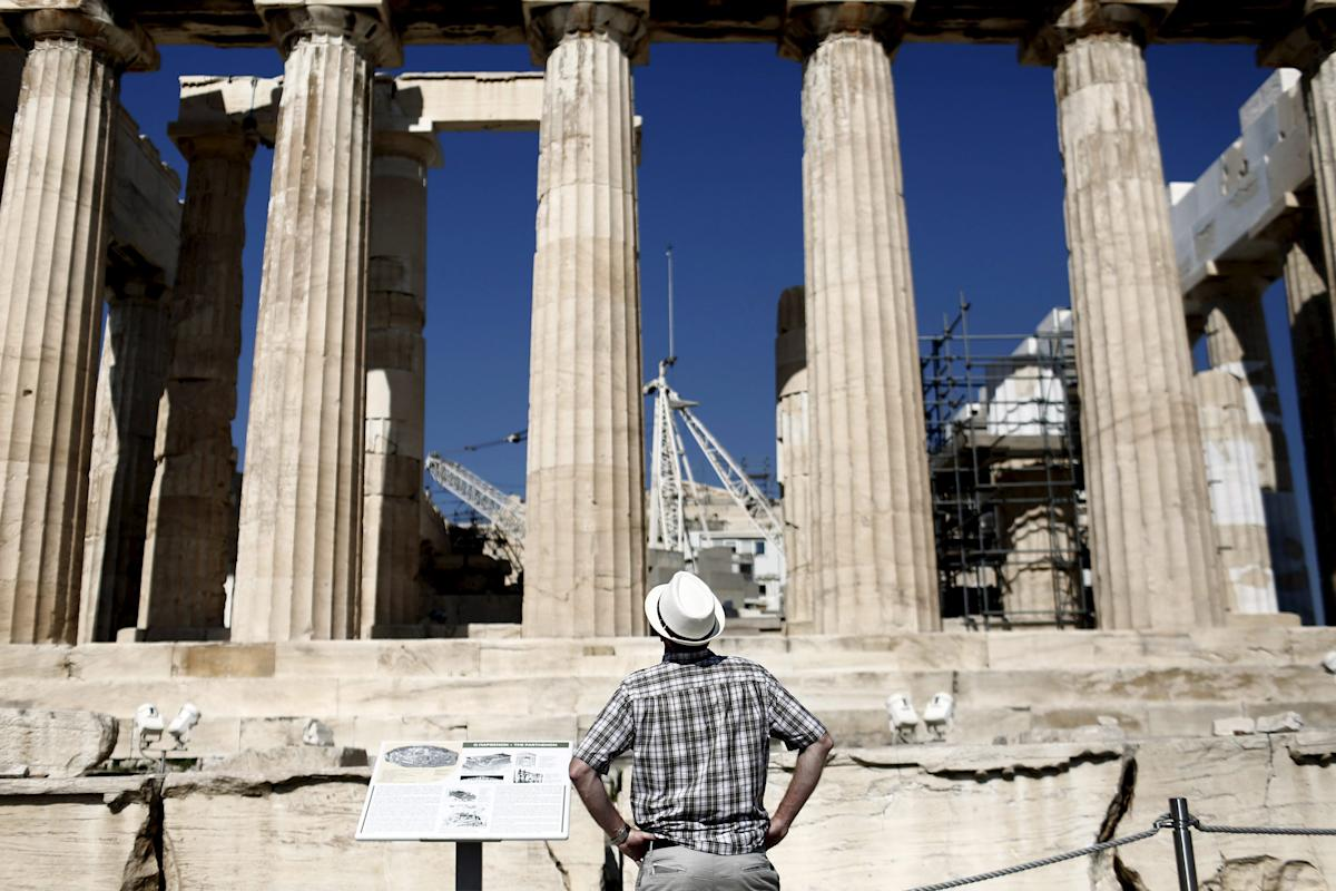 Visitor looks at the columns of the Parthenon temple atop the Acropolis hill in Athens