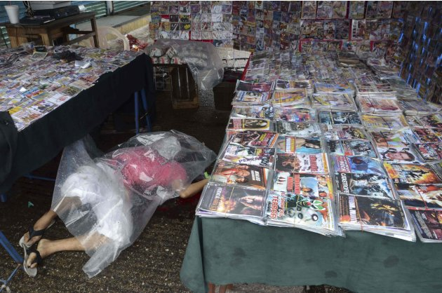 In this Thursday Sept. 22, 2011 file photo, a plastic sheet covers the body of a pirated DVD vendor at the central market in Acapulco, Mexico. The Pacific resort city of Acapulco has been hit by incre