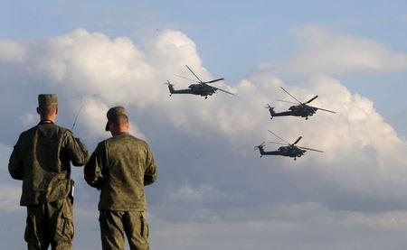 Russian servicemen watch Mi-28 military helicopters of the Berkuti aerobatic team fly during the opening of the Army-2015 international military forum...