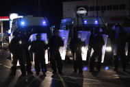 Riot police hold shields in front of Welsh police vans in Eltham, London, Wednesday, Aug. 10, 2011. A large group of local men gathered in the area on Wednesday to deter looters and a large number of police officers was also present to prevent any vigilante actions. (AP Photo/Matt Dunham)