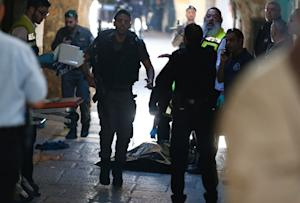 Israeli security forces and emergency personnel stand …