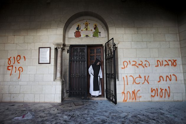 "FILE- In this Sept. 4, 2012, file photo, a Catholic monk stands in a doorway of the Latrun Trappist Monastery where Israeli police say vandals spray-painted anti-Christian and pro-settler graffiti and set the monastery's door on fire, in Latrun, between Jerusalem and Tel Aviv, Israel. After a series of attacks on Christian holy sites in Israel, Roman Catholic church officials recently issued a rare ""declaration"" calling on Israeli leaders to take action against vandalism and violence.(AP Photo/Oded Balilty, File)"