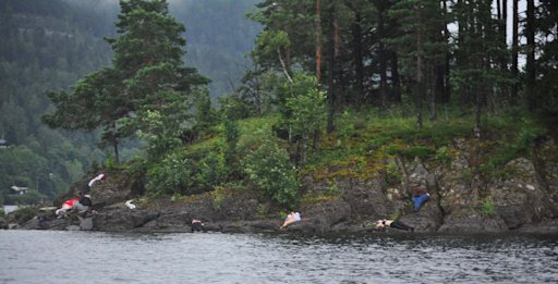 In this photo taken by Vergard M. Aas, a Norwegian crime reporter who responded to the scene of a mass shooting on Utoya Island, Norway, victims lie near the shoreline approximately one hour after police say a man dressed as a police officer gunned down youths as they ran and even swam for their lives at a camp which was organized by the youth wing of the ruling Labor Party, Friday July 22, 2011. Police say the suspect in this shooting set off a fatal explosion hours earlier in the Norwegian capital of Oslo. (AP Photo/Presse 3.0, Vegard M. Aas)