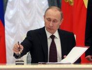 O presidente russo, Vladimir Putin, assina uma lei que ratifica a integração da Crimeia à Rússia, em uma cerimônia no Kremlin