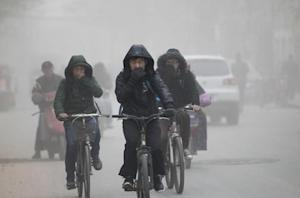 Residents cover their face from dust as they ride their bicycles along a street on a hazy day in Zhengzhou