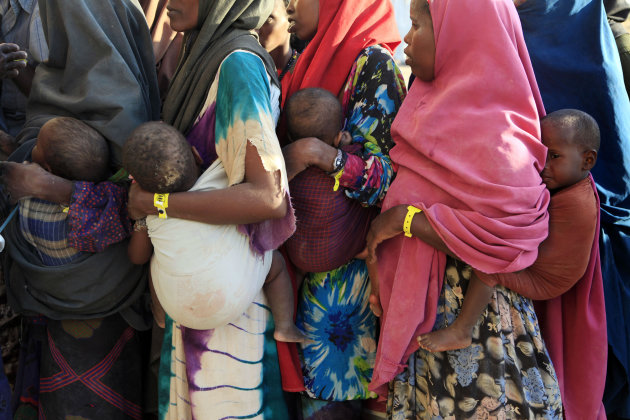 """Newly-arrived Somali refugees hold their babies as they wait in line to receive initial food aid, after registering as refugees at a reception center in Dagahaley Camp, outside Dadaab, Kenya, Tuesday, July 12, 2011. U.N. refugee chief Antonio Guterres said Sunday that drought-ridden Somalia is the """"worst humanitarian disaster"""" in the world, after meeting with refugees who endured unspeakable hardship to reach the world's largest refugee camp in Dadaab. (AP Photo/Rebecca Blackwell)"""
