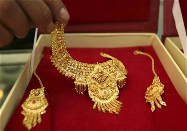 Shopkeeper displays gold jewellery for camera at jewellery shop in Jammu