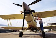 FILE - In this Monday, Sept. 17, 2001 file picture, Robert Williams of Mihand Aircraft near England, Ark., places the engine cover back on his agricultural airplane after removing the battery cable. Federal officials allowed crop-spraying planes to return to the skies as long as they stayed away from commercial airports, one day after they were grounded because of security concerns after the previous week's terrorist attacks. On Friday, Sept. 2, 2011, the FBI and Homeland Security have issued a nationwide warning about al-Qaida threats to small airplanes, just days before the anniversary of the 2001 terrorist attacks. (AP Photo/Spencer Tirey, File)