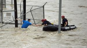 Rescue personnel grab the the hand of a man stranded …