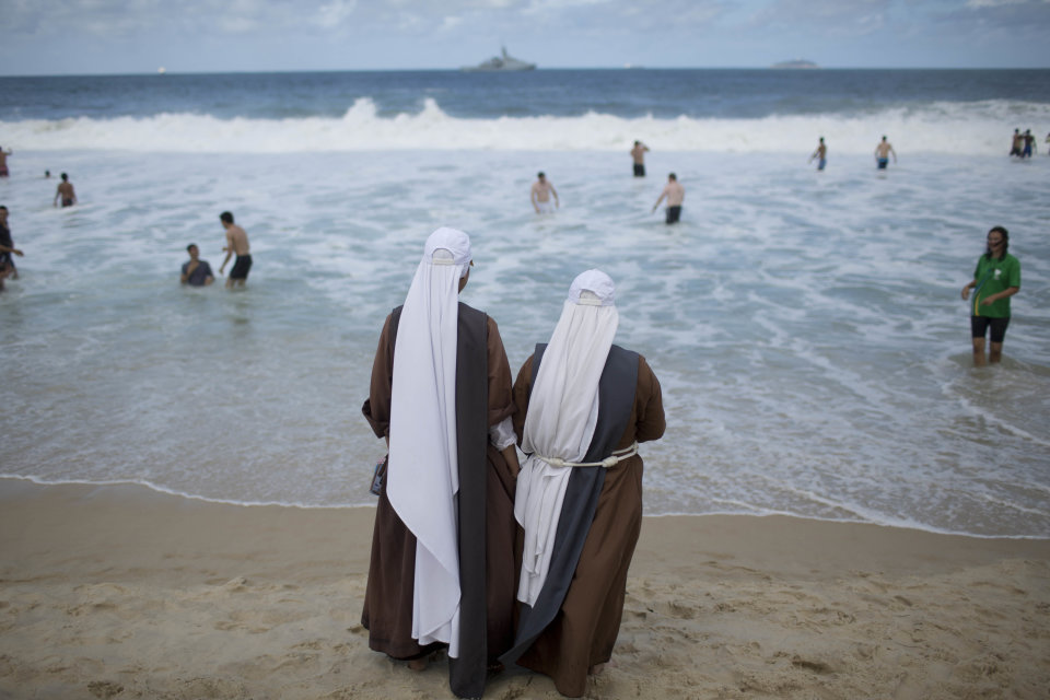 Nuns watch bathers on Copacabana beach as they wait for a night vigil service with Pope Francis for World Youth Day in Rio de Janeiro, Brazil, Saturday, July 27, 2013. Francis will preside over an evening vigil service on Copacabana beach that is expected to draw more than 1 million young people. (AP Photo/Felipe Dana)