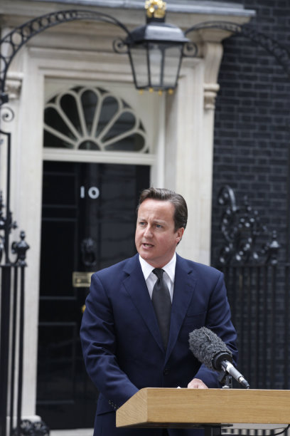 "British Prime Minister David Cameron addresses the media outside 10 Downing Street in London Tuesday, Aug. 9, 2011. Cameron announced the recall of Parliament from its summer recess to deal with the crisis touched off by three days of rioting in London. The Prime Minister described the scenes of burned buildings and smashed windows on the streets of London and several other British cities as ""sickening."" However, he refrained from ordering more extreme anti-rioting measures, such as calling in the military to help the beleaguered police restore order.(AP Photo/Elizabeth Dalziel)"