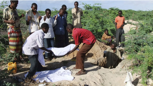 Relatives of Hassan Abdulkadir Adan,3rd left rear, from southern Somalia help to lower the body of his 7-year-old son into a grave in a refugee camp in Mogadishu, Somalia. Tuesday, Aug. 16, 2011. The World Food Program said Saturday that it is expanding food distribution efforts in famine-ravaged Somalia, where the U.N. has estimated that only 20 percent of people needing aid are able to receive it because an al-Qaida-linked group controls large portions of the country.(AP Photo/Farah Abdi Warsameh)