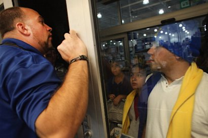 Best Buy shoppers await entering the store on Black Friday