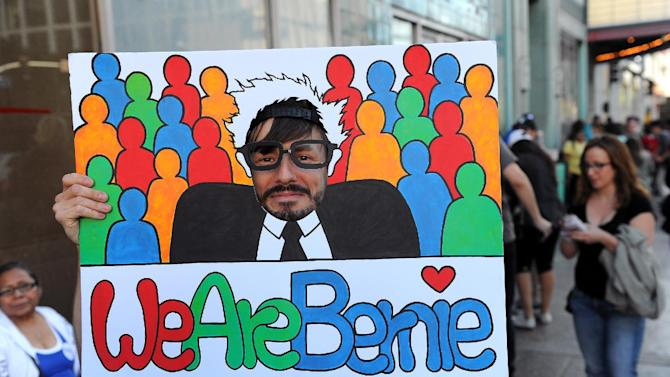 Scott Sorensen, of Echo Park, sticks his face in a Bernie Sanders sign before at rally for the Democratic presidential candidate, Wednesday, March 23, 2016, in Los Angeles. (AP Photo/Michael Owen Baker)