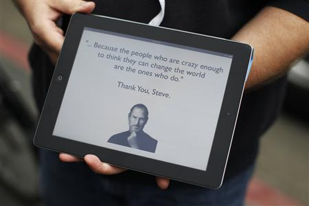 An Apple employee holds an iPad with its screen showing a message in memory of Apple founder Steve Jobs, in San Francisco