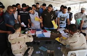 Iraqi men check in at the main army recruiting center …