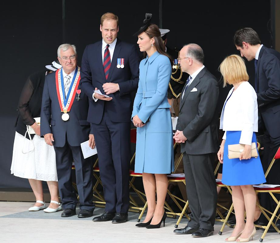 Britain's Prince William and Kate the Duchess of Cambridge, center, attend a remembrance ceremony in Arromanches, western France, Friday June 6, 2014, as part of the commemoration of the 70th anniversary of the D-Day landing. Visible at left is Arromanches mayor Patrick Jardin and at right French interior minister Bernard Cazeneuve. (AP Photo/Remy de la Mauviniere/Pool)