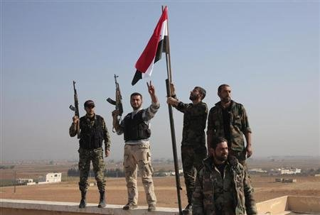 Forces loyal to Syria's President Bashar al-Assad hold up their weapons and erect a Syrian national flag at the village of al-Azizieh, on the northern edge of Safira, after capturing it from rebels, November 4, 2013. REUTERS/George Ourfalian