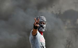 A Palestinian protester flashes the sign for victory …