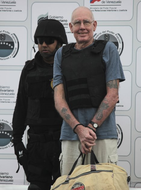 US citizen Scott Harris is escorted by a police officer during his deportation to the US at the Simon Bolivar airport in Maiquetia, near Caracas, Venezuela, Monday, Sept. 19, 2011. Harris is suspected