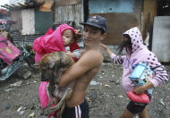 A family evacuate to safety with their pet dog at the height of typhoon Nesat Tuesday Sept. 27, 2011 in Manila, Philippines. Typhoon Nesat, with winds of up to 133 miles (215 kilometers), slammed the northeastern Philippines Tuesday, unleashing floods, cutting power, halting work in the capital and forcing thousands of residents to flee to evacuation centers. (AP Photo/Bullit Marquez)
