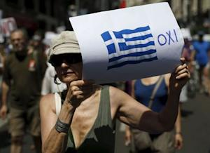 A woman holds a placard with a Greek national flag…