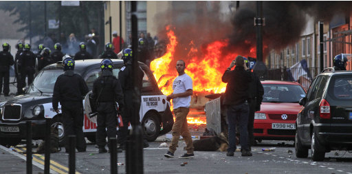 British police officers charge rioters, during riots in Hackney, east London, Monday Aug. 8, 2011. Youths set fire to shops and vehicles in a host of areas of London _ which will host next summer's Olympic Games _ and clashed with police in the nation's central city of Birmingham, as authorities struggled to halt groups of rampaging young people. (AP Photo/Lefteris Pitarakis)