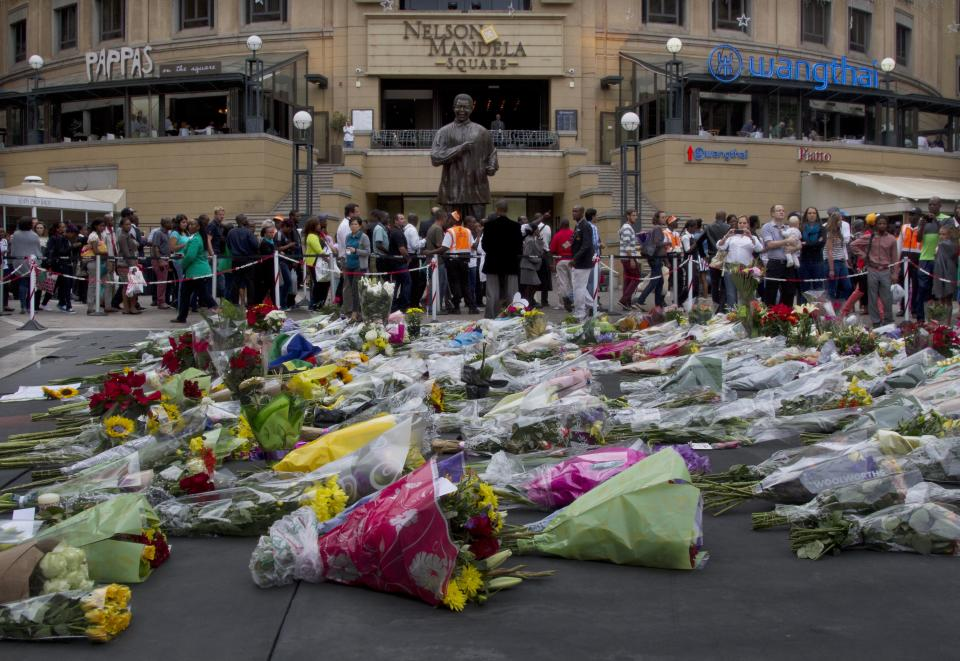 Floral tributes to former president Nelson Mandela, pile up beneath a statue of Mandela on Mandela Square at Sandton City, in Johannesburg Friday, Dec. 6, 2013. Mandela died Thursday at his Johannesburg home after a long illness. He was 95. (AP Photo/Athol Moralee)