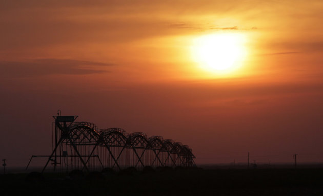 Sun rises behind an irrigation sprinkler near Lubbock, Texas, Thursday, Aug. 11, 2011. In parched West Texas, it's often easier to drill for oil than to find new sources of water.  After years of dimi