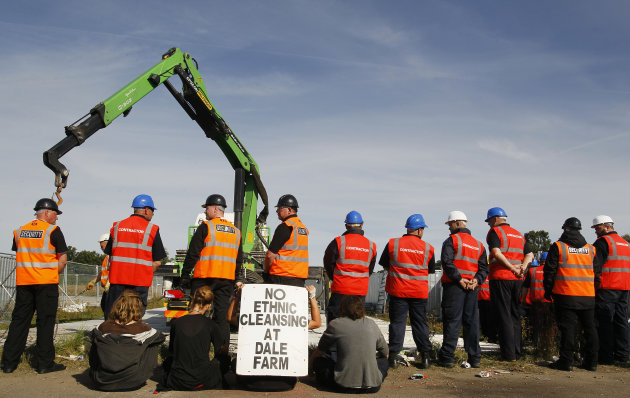 In this photo taken Thursday, Sept. 15, 2011, protestors sit and hold a banner as contractors and security put up fencing at Dale Farm travelers site, near Basildon, Essex, England. Within days, more
