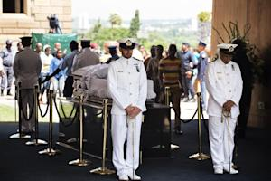 Navy officers stand guard by the coffin of South African…