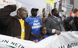 Floyd Dent, second from left, stands with protesters…