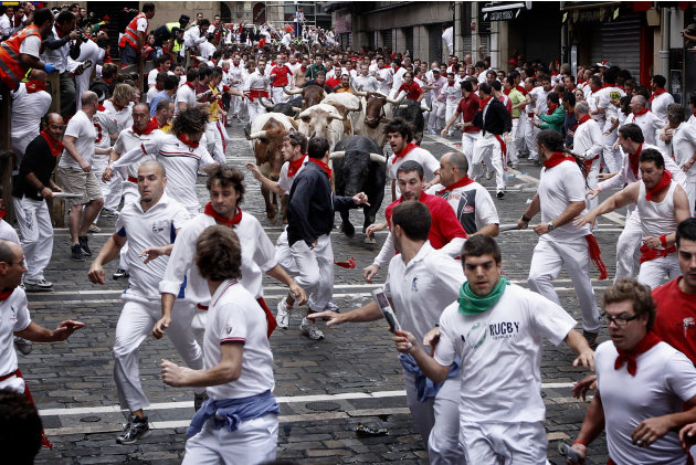 Revelers run next to Torrestrella ranch fighting bulls during the running of the bulls at the San Fermin fiestas on Thursday, July 7, 2011, in Pamplona, Spain. (AP Photo/Daniel Ochoa de Olza)