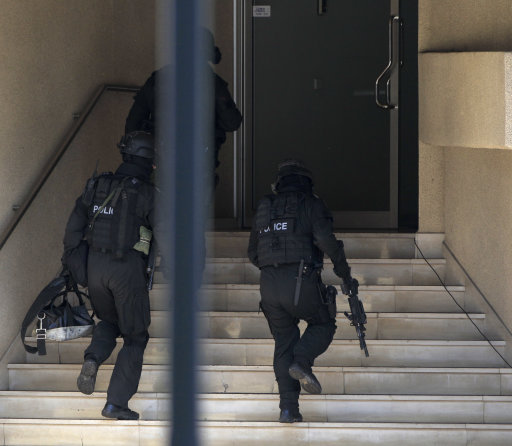 Police with automatic weapons rush into a building where a man is believed to be holding a child hostage at a lawyers office in suburban Sydney, Tuesday, Sept. 6, 2011. Australian police cordoned off a Sydney building Tuesday in a tense standoff with the man who claimed to have a bomb, smashed a window and issued threats from the lawyer's office where he holed up with his teenage daughter. (AP Photo/Rick Rycroft)