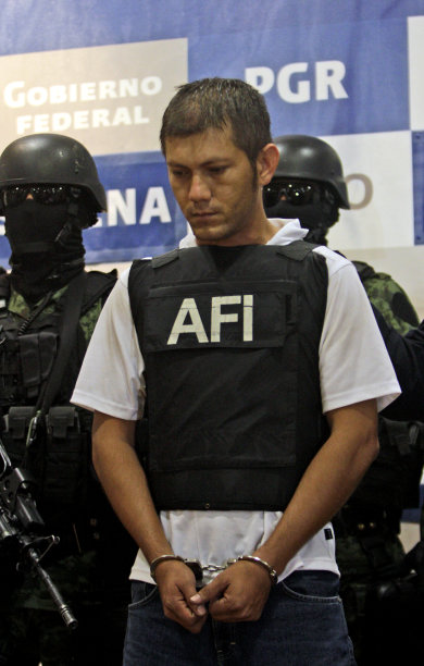Federal police officers escort Ricardo Benitez Servin aka 'El Mudo', upon his presentation to the press in Mexico City, Monday, Aug. 15, 2011. Benitez is the alleged lieutenant of the Beltran Leyva drug cartel for the area known as Costa Grande in Mexico's Guerrero state. (AP Photo/Arnulfo Franco)