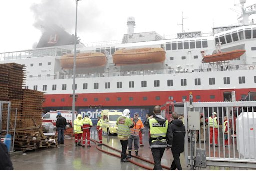 Smoke rises from the Norwegian cruise ship, MS Nordlys, one of the classic Hurtigruten ships alongside in Alesund in western Norway, Thursday Sept. 15, 2011 as firefighters and police attend. The Sunnmore police district says that 106 passengers were evacuated into lifeboats before the vessel managed to dock into the port of Alesund. The rest of the passengers and crew were being evacuated. Police said no one was killed but three people were taken to hospital. The fire broke out in the engine room at 9.20 a.m. (0720 GMT). (AP Photo/Scanpix)  NORWAY OUT